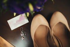 Γαμήλια εξαρτήματα: παπούτσια και μια ανθοδέσμη της νύφης Όμορφη ιώδης γαμήλια ανθοδέσμη Μπεζ παπούτσια και διακοσμήσεις Στοκ φωτογραφία με δικαίωμα ελεύθερης χρήσης