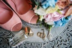 Γαμήλια εξαρτήματα, σκουλαρίκια, άρωμα, ανθοδέσμη και ρόδινα παπούτσια Στοκ φωτογραφίες με δικαίωμα ελεύθερης χρήσης