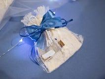 Γαμήλια εύνοια που διακοσμείται με τη δαντέλλα και την μπλε κορδέλλα στοκ εικόνα