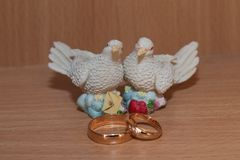Γαμήλια χρυσά δαχτυλίδια και άγαλμα με τα περιστέρια Στοκ Φωτογραφίες