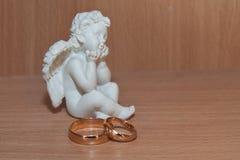 Γαμήλια χρυσά δαχτυλίδια και statuette ενός αγγέλου Στοκ Φωτογραφία