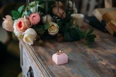 Γαμήλια χρυσά δαχτυλίδια σε ένα διακοσμητικό μαξιλάρι με την κινηματογράφηση σε πρώτο πλάνο λουλουδιών Έννοια κοσμήματος Στοκ Φωτογραφία