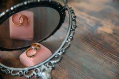 Γαμήλια χρυσά δαχτυλίδια σε ένα διακοσμητικό μαξιλάρι με την κινηματογράφηση σε πρώτο πλάνο λουλουδιών Έννοια κοσμήματος Στοκ Φωτογραφίες