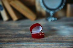 Γαμήλια χρυσά δαχτυλίδια σε ένα διακοσμητικό μαξιλάρι με την κινηματογράφηση σε πρώτο πλάνο λουλουδιών Έννοια κοσμήματος Στοκ φωτογραφίες με δικαίωμα ελεύθερης χρήσης