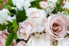 Γαμήλια χρυσά δαχτυλίδια σε μια ανθοδέσμη των λουλουδιών στοκ εικόνες