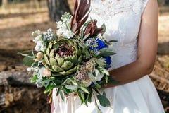 Γαμήλια όμορφη ανθοδέσμη του protea στα χέρια της νύφης closeup Στοκ Φωτογραφία
