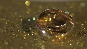 Γαμήλια gols δαχτυλίδια που βρίσκονται στη λαμπρή στιλπνή επιφάνεια Να λάμψει με το φως E απόθεμα βίντεο