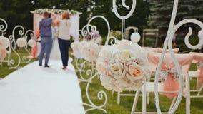 Γαμήλιες διακοσμήσεις για μια εορταστική τελετή υπαίθρια Διακοσμήσεις στις καρέκλες Η νύφη και ο νεόνυμφος που στέκονται κάτω από απόθεμα βίντεο