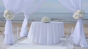 Γαμήλιες διακοσμήσεις των άσπρων υφασμάτων και των λουλουδιών στην παραλία πριν από την τελετή απόθεμα βίντεο