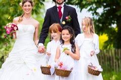 Γαμήλιες ζεύγος και παράνυμφος που πλημμυρίζουν τα λουλούδια Στοκ εικόνα με δικαίωμα ελεύθερης χρήσης