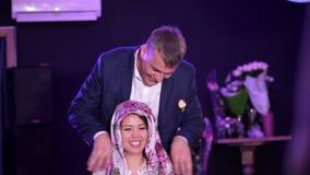 Γαμήλιες παραδόσεις, τελετές ο νεόνυμφος φορά, δένει ένα μαντίλι, ένα μαντίλι για το κεφάλι στο κεφάλι της νύφης, στο τέλος απόθεμα βίντεο