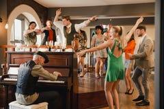 Γαμήλιοι φιλοξενούμενοι που έχουν τη διασκέδαση με το πιάνο στοκ φωτογραφία