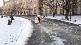 γαμήλιος χειμώνας νεόνυμφων νυφών υπαίθρια Η εναέρια άποψη, το ζεύγος στα γαμήλια φορέματα τρέχει με τα ζωηρόχρωμα μπαλόνια μέσω  απόθεμα βίντεο