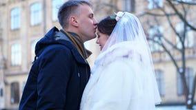 γαμήλιος χειμώνας νεόνυμφων νυφών υπαίθρια το ζεύγος στα γαμήλια φορέματα ο νεόνυμφος φιλά ήπια τη νύφη στο μέτωπο, αγκάλιασμα Εί φιλμ μικρού μήκους