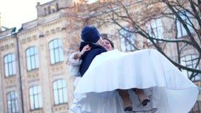 γαμήλιος χειμώνας νεόνυμφων νυφών υπαίθρια το ζεύγος στα γαμήλια φορέματα ο νεόνυμφος κρατά τη νύφη στα όπλα του, περιστροφή είνα απόθεμα βίντεο