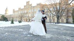 γαμήλιος χειμώνας νεόνυμφων νυφών υπαίθρια το ζεύγος στα γαμήλια φορέματα είναι γαμήλιος χορός χορού σε ένα χιονισμένο πάρκο, ενά απόθεμα βίντεο