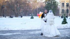 γαμήλιος χειμώνας νεόνυμφων νυφών υπαίθρια το ζεύγος στα γαμήλια φορέματα είναι γαμήλιος χορός χορού σε ένα χιονισμένο πάρκο, ενά φιλμ μικρού μήκους