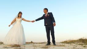 Γαμήλιος χορός στο μήνα του μέλιτος Ρομαντικός χορός χορού ανδρών και γυναικών στην άμμο ενάντια στον ουρανό απόθεμα βίντεο