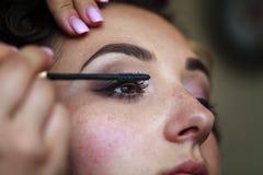 Γαμήλιος makeup καλλιτέχνης που κάνει να αποζημιώσει τη νύφη Στοκ Φωτογραφίες