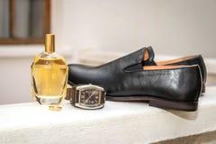 Γαμήλιο δαχτυλίδι γαμπρού, άρωμα, ρολόι και μαύρο παπούτσι δέρματος στοκ φωτογραφίες