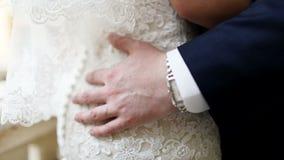 Γαμήλιο ζεύγος που αγκαλιάζει, η νύφη που κρατά μια ανθοδέσμη των λουλουδιών στο χέρι της απόθεμα βίντεο
