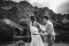 Γαμήλιο ζεύγος που περπατά και που κρατά τα χέρια στην ακτή λιμνών Ηλιόλουστη ημέρα στα βουνά Tatra r στοκ εικόνα