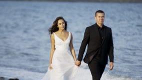 Γαμήλιο ζεύγος που περπατά στην παραλία απόθεμα βίντεο