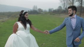 Γαμήλιο ζεύγος που τρέχει κοντά στον ποταμό βουνών Νεόνυμφος και νύφη ερωτευμένοι απόθεμα βίντεο