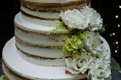 Γαμήλιο κέικ βανίλιας που διακοσμείται με τα λουλούδια στοκ εικόνες με δικαίωμα ελεύθερης χρήσης