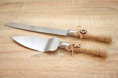Γαμήλιο μαχαίρι και φτυάρι κέικ που διακοσμείται στον ξύλινο πίνακα Στοκ εικόνα με δικαίωμα ελεύθερης χρήσης