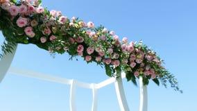Γαμήλιο ντεκόρ, άσπρη γαμήλια αψίδα που διακοσμείται με τα τριαντάφυλλα, γαμήλια τελετή στην παραλία, προετοιμασία για τη γαμήλια φιλμ μικρού μήκους