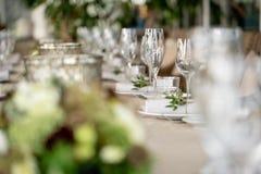 Γαμήλιο συμπόσιο ή γεύμα gala Οι καρέκλες και ο πίνακας για τους φιλοξενουμένους, που εξυπηρετούνται με τα μαχαιροπήρουνα και τα  στοκ εικόνες