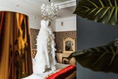 Γαμήλιο φόρεμα νυφών στον πολυέλαιο στοκ εικόνες με δικαίωμα ελεύθερης χρήσης