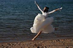 Γαμήλιο φόρεμα στην τρέχοντας ευτυχή γυναίκα στο νερό θερινών παραλιών Στοκ εικόνες με δικαίωμα ελεύθερης χρήσης