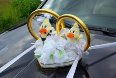 Γαμήλιο limousine που διακοσμείται με τα λουλούδια και τα χρυσά δαχτυλίδια Στοκ φωτογραφίες με δικαίωμα ελεύθερης χρήσης