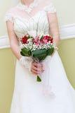 Γαμήλια δέσμη των λουλουδιών στα χέρια της νύφης Στοκ Φωτογραφία