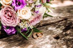 Γαμήλια ανθοδέσμη και δαχτυλίδια στην ξύλινη επιφάνεια Στοκ Φωτογραφίες