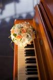 Γαμήλια ανθοδέσμη κρητιδογραφιών με τα πορτοκαλιά τριαντάφυλλα στο πιάνο Στοκ φωτογραφίες με δικαίωμα ελεύθερης χρήσης