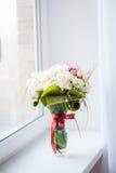 Γαμήλια ανθοδέσμη με τα τριαντάφυλλα που στέκονται σε ένα παράθυρο Στοκ Εικόνες