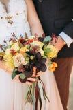 Γαμήλια ανθοδέσμη μόδας φθινοπώρου στα χέρια της νύφης και του νεόνυμφου Στοκ φωτογραφία με δικαίωμα ελεύθερης χρήσης
