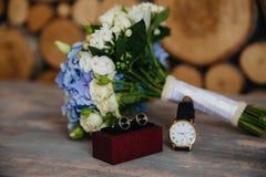 Γαμήλια ανθοδέσμη, νεόνυμφοι wristwatch, μανικετόκουμπα στο γκρίζο υπόβαθρο Έννοια των γαμήλιων εξαρτημάτων στοκ εικόνες με δικαίωμα ελεύθερης χρήσης