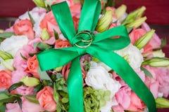Γαμήλια ανθοδέσμη (λουλούδια) με τα χρυσά δαχτυλίδια και το πράσινο τόξο στην κορυφή Στοκ φωτογραφία με δικαίωμα ελεύθερης χρήσης
