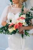 Γαμήλια ανθοδέσμη στο άσπρο γαμήλιο φόρεμα στα χέρια της όμορφης νύφης Στοκ φωτογραφία με δικαίωμα ελεύθερης χρήσης