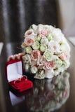Γαμήλια ανθοδέσμη τριαντάφυλλων και δύο γαμήλιων δαχτυλιδιών Στοκ Εικόνα