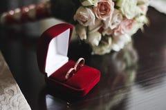 Γαμήλια ανθοδέσμη τριαντάφυλλων και δύο γαμήλιων δαχτυλιδιών Στοκ Εικόνες