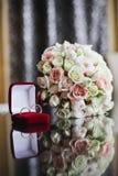 Γαμήλια ανθοδέσμη τριαντάφυλλων και δύο γαμήλιων δαχτυλιδιών Στοκ Φωτογραφία