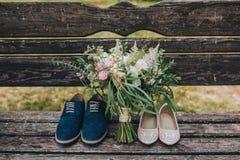 Γαμήλια ανθοδέσμη των λουλουδιών και της πρασινάδας και της νύφης και του νεόνυμφου παπουτσιών που βρίσκονται σε έναν παλαιό ξύλι στοκ εικόνες