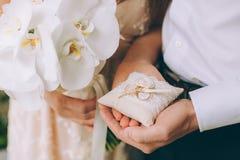 Γαμήλια δαχτυλίδια εκμετάλλευσης ανδρών και γυναικών Στοκ Φωτογραφία