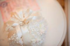 Γαμήλια δαχτυλίδια ενός πρόσφατα-παντρεμένου ζεύγους σε ένα μαξιλάρι για τα δαχτυλίδια Στοκ εικόνα με δικαίωμα ελεύθερης χρήσης
