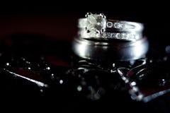 Γαμήλια δαχτυλίδια διαμαντιών στο μαύρο κατασκευασμένο υπόβαθρο στοκ εικόνα